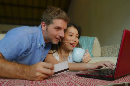 Photo pour Young happy and beautiful mixed ethnicity couple with Caucasian husband or boyfriend and Asian Chinese woman wife or girlfriend shopping online together at home with laptop computer - image libre de droit