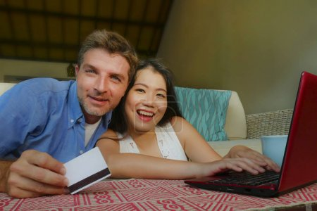 Photo for Young happy and beautiful mixed ethnicity couple with Caucasian husband or boyfriend and Asian Chinese woman wife or girlfriend shopping online together at home with laptop computer - Royalty Free Image