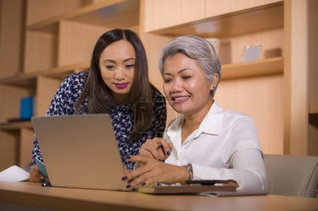 Photo for Natural lifestyle portrait of two business partners or work colleagues women collaborating and coworking happy and cheerful at office laptop computer desk in female job collaboration - Royalty Free Image
