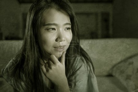 Photo for Dramatic lifestyle portrait of young sad and depressed Asian Japanese woman crying desperate sitting at home sofa couch suffering depression problem and anxiety crisis burst into tears - Royalty Free Image