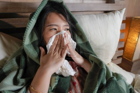 Foto de Retrato de estilo de vida de joven hermosa enfermo y agotado mujer coreana asiática que sufre frío y gripe teniendo temperatura acostada en la cubierta de la cama con manta estornudando la nariz con papel tisú - Imagen libre de derechos