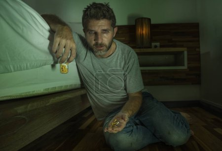 Photo for Dramatic home portrait of young desperate and depressed lonely man sitting on bedroom floor crying sick suffering depression problem taking pills feeling wasted thinking about suicide by overdose - Royalty Free Image