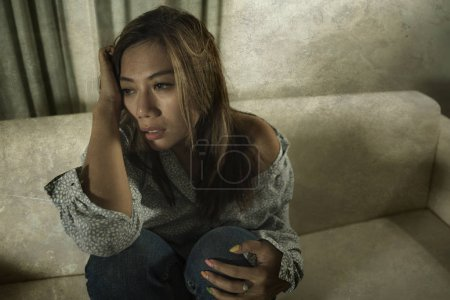 Photo for Young beautiful sad and depressed Asian woman in pain thoughtful and confused at home couch feeling broken heart suffering depression crisis and anxiety problem - Royalty Free Image