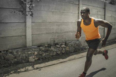 Photo pour Entraînement de coureur urbain. Jeune homme afro-américain noir attrayant et athlétique courant à l'extérieur sur route asphaltée entraînement jogging dur dans le sport sacrifice engagement et mode de vie sain concept - image libre de droit