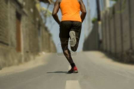 Photo for Urban runner workout . Back view of athletic black African American professional sport man running training hard outdoors on asphalt road during jogging workout in healthy lifestyle - Royalty Free Image