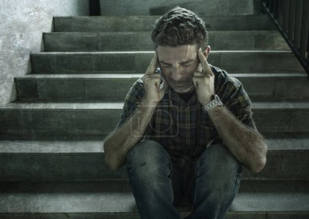 Photo for Dramatic portrait of young depressed and paranoid man sitting outdoors on dark grunge street corner staircase feeling sick suffering depression problem and anxiety crisis in mental health concep - Royalty Free Image