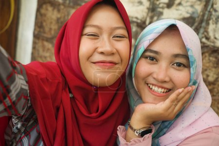 Photo for Muslim teenager student girlfriends selfie. Happy and pretty Asian Indonesian girls in traditional Islamic hijab head scarf taking selfie together having fun at cafe in friendship and social media concept - Royalty Free Image