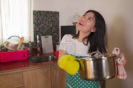 Photo for Asian home cook girl lifestyle portrait . Young happy and beautiful Korean woman in kitchen apron and glove holding cooking pot excited and satisfied preparing soup delighted with delicious recipe - Royalty Free Image