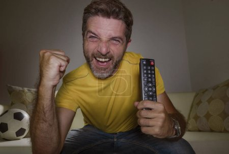 Photo for Portrait at home of young happy and excited man watching European football game on TV celebrating goal on couch screaming spastic gesturing crazy cheerful as soccer fan enjoying victory - Royalty Free Image