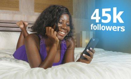 Photo pour Une jeune Afro-américaine noire, heureuse et cool, couchée détendue au lit à l'aide d'un téléphone mobile sur Internet sourire joyeuse mise en réseau amener les adeptes des médias sociaux à influencer le mode de vie - image libre de droit