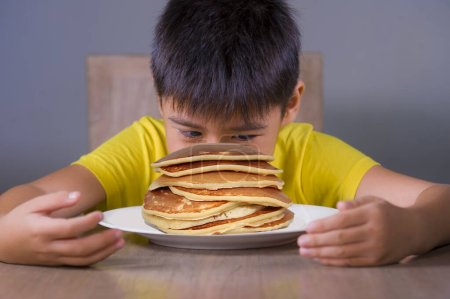 Photo for Young boy having pancakes breakfast. 7 or 8 years old happy and excited child sitting on table eating huge pile of pancakes smiling naughty in sugar abuse and unhealthy nutrition - Royalty Free Image
