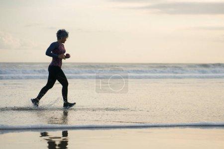 Foto de Silueta de mujer de mediana edad corriendo en la playa - señora madura atractiva de 40 o 50 años haciendo ejercicio de jogging disfrutando de fitness y estilo de vida saludable en el hermoso paisaje del atardecer del mar - Imagen libre de derechos