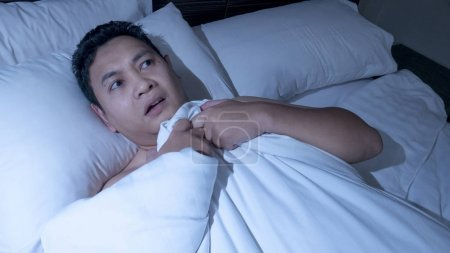 Photo for Portrait od Asian man depressed frustrated and hard to sleep on the bed in the midnight - Royalty Free Image