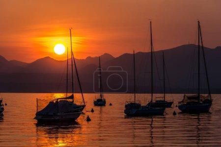 Sailing Boats on lake Garda with sunset, Italy