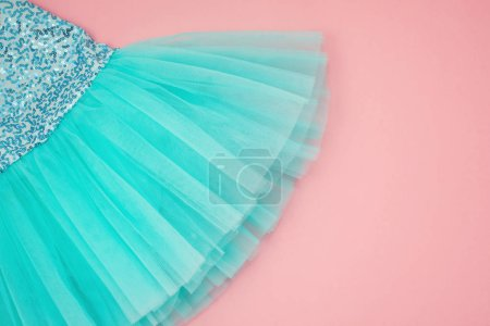 Top view of girl ballet tutu dress on pink background
