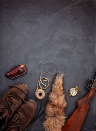 Plat laïque avec des munitions de chasse sur le fond gris: vieilles bottes, chapeau, fusil, couteau, corde, courroie, queue de renard. Vue de dessus