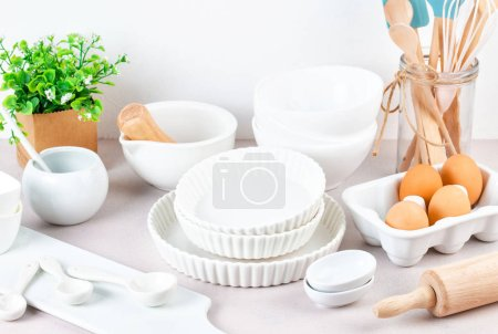 Still life with different white bowls, kitchen tools on white table.Various kitchen utensils.