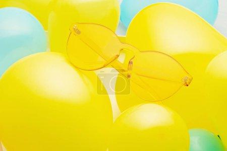 Foto de Vista superior de gafas de sol amarillas de moda sobre el fondo pastel hecha sin globos amarillos y azules - Imagen libre de derechos