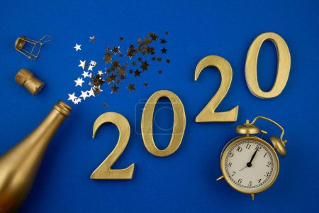 Photo for Top view 2020 figures, Golden bottle of champagne, glass, alarm clock and confettie. Party, new year, celebration concept - Royalty Free Image