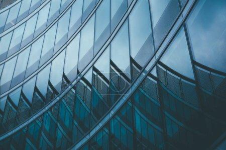 Photo pour Abstrait business ville moderne urbain futuriste architecture fond. Concept immobilier, flou de mouvement, réflexion en verre de façade gratte-ciel de grande hauteur, image bleue tonique avec bokeh - image libre de droit
