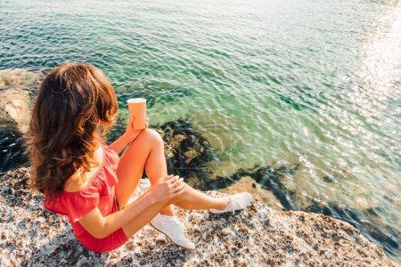 Photo pour Fille assise sur le rocher avec un café à emporter et regardant la mer et le lever ou le coucher du soleil tranquillité d'esprit, se détendre sur le bord de la mer et concepts de méditation image chaude et ensoleillée avec espace de copie - image libre de droit
