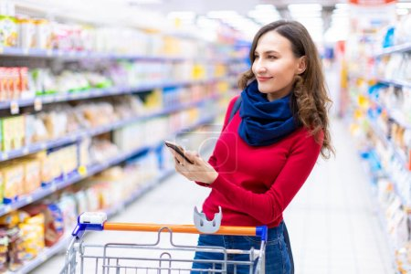 Photo for Young smiling woman shopping in a supermarket looking at the screen of the phone her shopping list (grocery list) - consumerism and choosing concept - Royalty Free Image