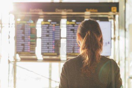 Photo pour Vue arrière d'une jeune femme regardant le tableau d'information de vol à l'aéroport - image libre de droit