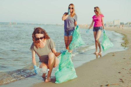 Photo pour Image de jeunes femmes volontaires ramassant (nettoyage) des ordures en plastique sur la plage - sauver la terre, l'écologie et le concept de recyclage du plastique - image libre de droit