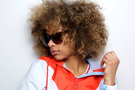 Close up side portrait of cool young african american woman with sunglasses posing against white wall