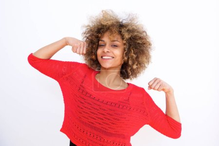 Portrait of beautiful african american girl smiling and flexing bicep muscle