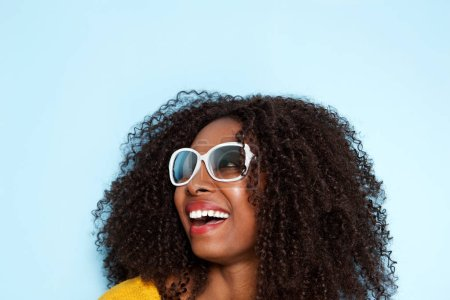 Close up portrait of cheerful young african woman in sunglasses looking away and laughing on blue background