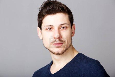 Foto de Retrato de hombre joven con expresión grave contra el fondo gris de cerca - Imagen libre de derechos