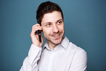 Close up portrait of young businessman talking on cellphone