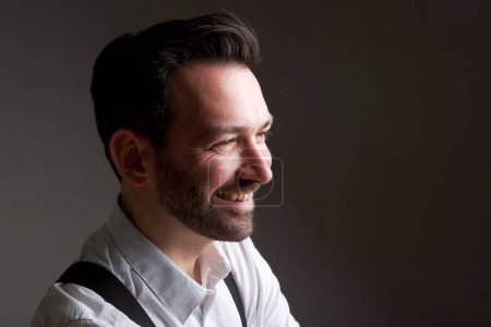 Side portrait of handsome man with beard smiling against gray background