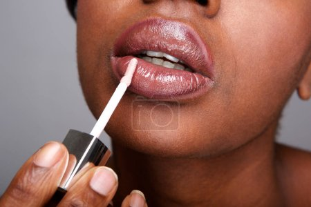 Close up partial portrait of beautiful african american woman applying shiny lip gloss