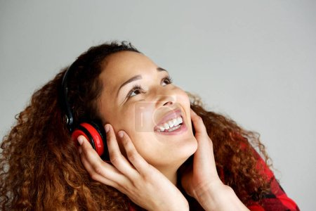 Close up portrait of happy young african american woman listening to music with headphones and looking up