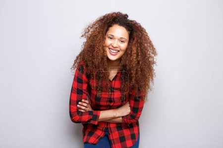 Portrait of happy young woman with curly hair smiling against gray background