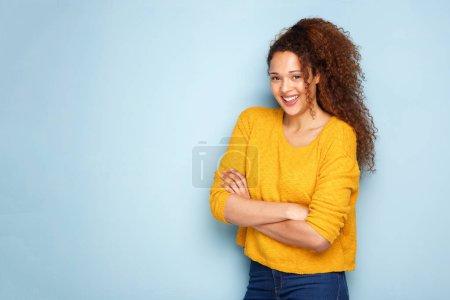 Foto de Retrato de mujer joven con el pelo rizado sonriendo por la pared azul con los brazos cruzados - Imagen libre de derechos