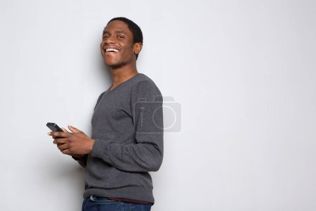 Photo for Profile portrait of happy african american man with cellphone against white background - Royalty Free Image