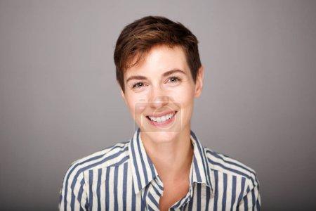 Photo pour Gros plan portrait avant de jeune femme souriant sur fond gris - image libre de droit