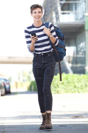 Photo for Full length portrait of happy young woman with bag holding cellphone - Royalty Free Image
