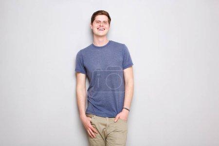 Photo pour Portrait de jeune homme souriant debout près du mur gris - image libre de droit