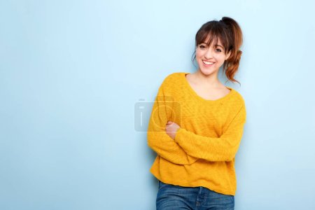 Photo for Portrait of smiling young woman with arms crossed against blue background - Royalty Free Image