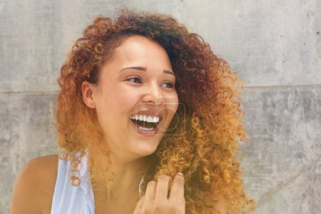 Close up portrait of happy young woman with curtly hair laughing