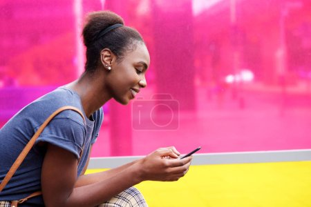Photo for Side portrait smiling african american woman looking at mobile phone - Royalty Free Image