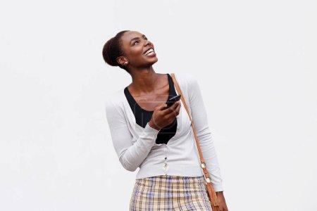 Photo pour Portrait de jeune femme noire, souriant avec téléphone portable sur fond blanc isolé - image libre de droit