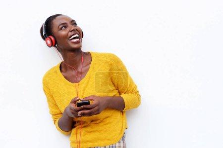 Photo pour Portrait de jeune femme africaine souriante écoutant de la musique avec écouteurs et téléphone portable sur fond blanc isolé - image libre de droit