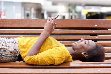 Photo for Portrait of beautiful young african american woman lying on bench looking at mobile phone - Royalty Free Image