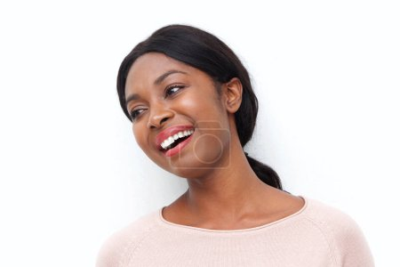 Photo for Close up portrait of happy young black woman laughing and looking the side against white background - Royalty Free Image