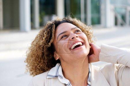 Porträt einer fröhlichen jungen afrikanisch-amerikanischen Frau, die draußen lacht